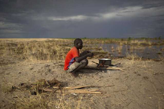 A Turkana man sits on the shore of Lake Turkana, some kilometres from Todonyang near the Kenya-Ethiopia border in northwestern Kenya October 12, 2013. (Photo by Siegfried Modola/Reuters)