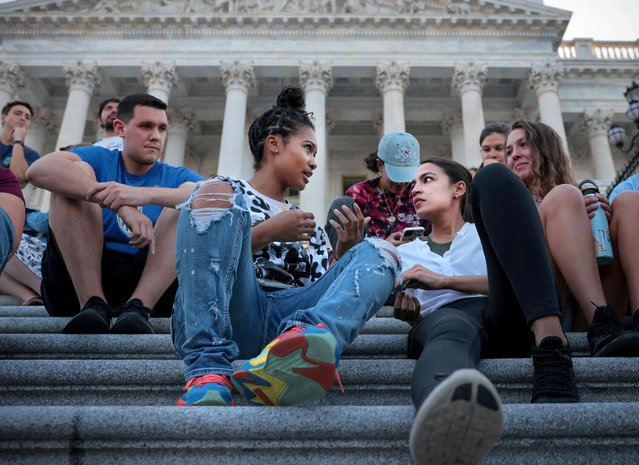 Representative Alexandria Ocasio-Cortez (D-NY), talks with Kamala Lyles, 20, during a demonstration outside the U.S. Capitol to protest the expiration of the federal moratorium on residential evictions, in Washington, U.S., August 2, 2021. (Photo by Evelyn Hockstein/Reuters)