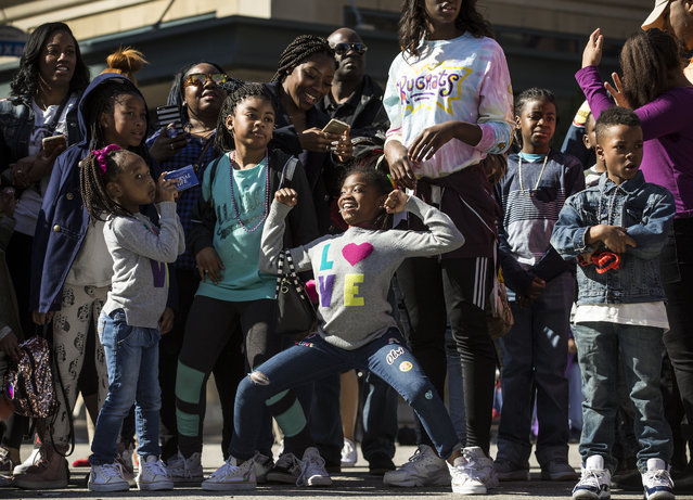 "In this Monday, January 15, 2018 photo, people line Texas Avenue to watch The ""Original"" MLK, Jr. Parade in Houston. For more than two decades, competing MLK Day parades have been held in Houston. This year, the city of Houston threw its official support behind one parade, the 41st annual ""Original"" MLK, Jr. Parade, hoping the city could unite behind only one parade. But organizers of the other parade, the 25th annual MLK Grande Parade, will still be holding its event and they say they have no plans to stop having their own parade. (Photo by Brett Coomer/Houston Chronicle via AP Photo)"