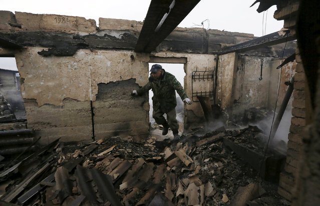 Local resident Sergei Shvedchikov, 61, enters his burnt house to collect scrap metal in the settlement of Shyra, damaged by recent wildfires, in Khakassia region, April 13, 2015. (Photo by Ilya Naymushin/Reuters)
