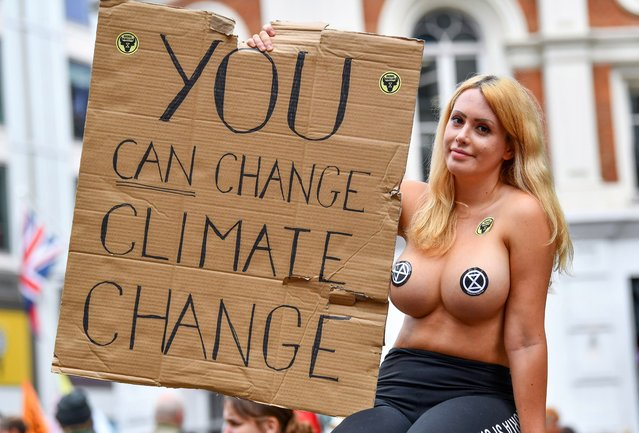 """An Extinction Rebellion protestor holds up a sign saying """"You Can Change Climate Change"""" in St Martin's Lane in London, Britain on August 23, 2021. (Photo by James Veysey/Rex Features/Shutterstock)"""