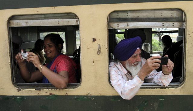 Indian Sikh pilgrims take pictures as they arrive at the Wagah border railway station in Pakistan, to attend the Baisakhi festival in Lahore April 11, 2015. Hundreds of Sikh pilgrims arrived into Pakistan to celebrate the festival at the shrines of Panja Sahib and Nankana Sahib, the birth place of Sikh faith founder Guru Nanak Dev. Baisakhi is the beginning of the solar year in the Indian state of Punjab. (Photo by Mohsin Raza/Reuters)