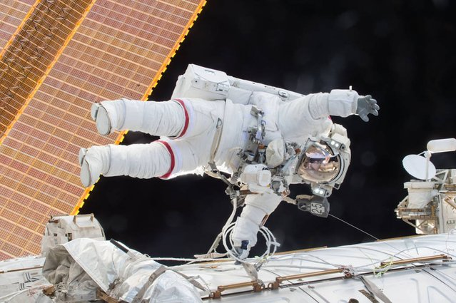 "This NASA image released December 22, 2015 shows Expedition 46 Commander Scott Kelly on a December 21, 2015 spacewalk, in which Kelly and Flight Engineer Tim Kopra successfully moved the International Space Station's mobile transporter rail car ahead of Wednesday's docking of a Russian cargo supply spacecraft. After quickly completing their primary objective for the spacewalk, Kelly and Kopra tackled several additional ""get-ahead"" tasks. Kelly routed a second pair of cables in preparation for International Docking Adapter installment work to support US commercial crew vehicles. (Photo by AFP Photo/NASA)"