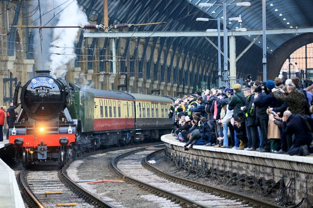 """People watch from a railway platform as the Flying Scotsman steam engine prepares to leave Kings Cross station in London, February 25, 2016. Celebrity locomotive 60103 Flying Scotsman made its official return to steam with a celebratory """"Inaugural Run"""" along the East Coast Mainline after a decade-long 4.2 million British Pounds ($5.8 million) restoration. (Photo by Paul Hackett/Reuters)"""