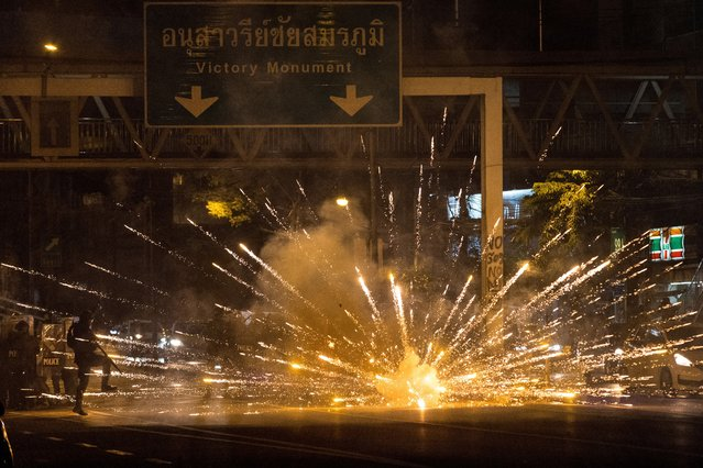 Fireworks, thrown by protesters, explode in front of a line of police during a demonstration against Thai Prime Minister Prayut Chan-O-Cha and his government's handling of the Covid-19 coronavirus crisis in Bangkok on September 6, 2021. (Photo by Jack Taylor/AFP Photo)