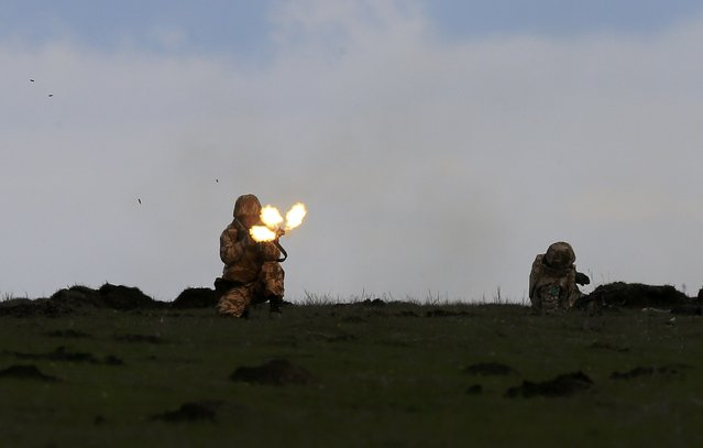 "A soldier fires his weapon during the ""Wind Spring 15"" military exercises at Smardan shooting range April 21, 2015. (Photo by Radu Sigheti/Reuters)"