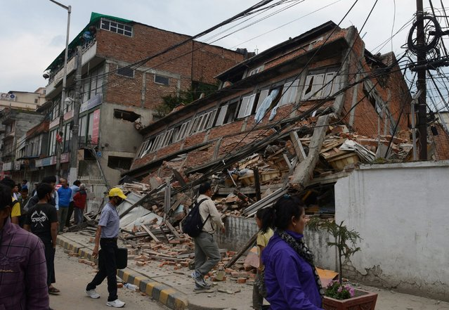 Nepalese people walk past a collapsed bullding in Kathmandu after an earthquake on April 25, 2015. (Photo by Prakash Mathema/AFP Photo)