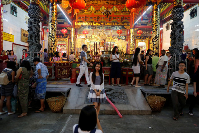 A girl has a photo taken by her friend as they visit a temple during the Chinese Lunar New Year's festival in Chinatown, in Yangon, Myanmar January 27, 2017. (Photo by Soe Zeya Tun/Reuters)