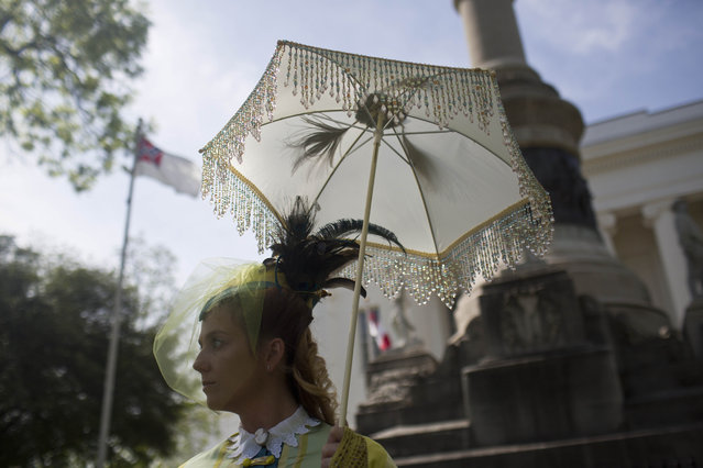 United Daughters of the Confederacy member, Carrie McGough, of Titus, Ala., stands in front of the Alabama Capitol building during a confederate memorial day ceremony Monday, April 27, 2015, in Montgomery, Ala. McGough said she designed and sewed her attire to look like an authentic Civil War era dress. (Photo by Brynn Anderson/AP Photo)