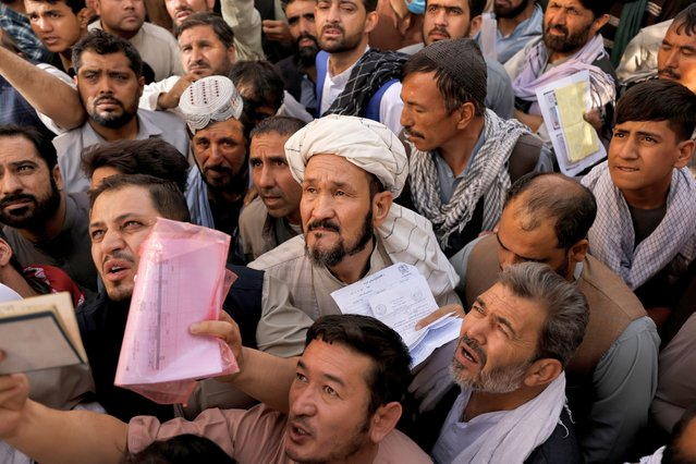 Afghans gather outside the passport office after Taliban officials announced they will start issuing passports to its citizens again, following months of delays that hampered attempts by those trying to flee the country after the Taliban seized control, in Kabul, Afghanistan on October 6, 2021. (Photo by Jorge Silva/Reuters)