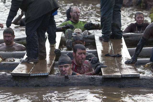"""Competitors makes their way through a water obstacle during the annual Tough Guy race """"the toughest race in the world"""" at Perton in Staffordshire, England, Sunday January 26, 2014. Tough Guy claims to be the world's most demanding one-day survival ordeal. First staged in 1987, the Tough Guy Challenge has been widely described as one of the hardest races of it's type with up to one-third of the starters failing to finish in a typical year. (Photo by Jon Super/AP Photo)"""