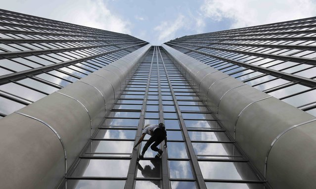 """French climber Alain Robert, also known as """"Spiderman"""", scales the Tour Montparnasse, a 210-metre (689 ft) building in central Paris, France April 28, 2015. Robert scaled the tower with a Nepal flag in tribute to the victims of the recent earthquake. (Photo by Gonzalo Fuentes/Reuters)"""