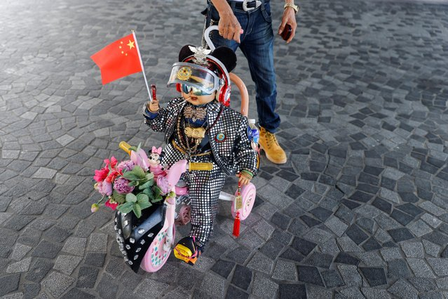 A pro-China supporter pushes a doll with Chinese flag on Chinese National Day, in Hong Kong, China, October 1, 2021. (Photo by Tyrone Siu/Reuters)