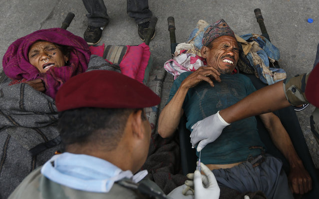 An Indian army doctor administers an injection to an injured man after he was evacuated from higher reaches of mountains by Nepalese army, in Kathmandu, Nepal, Wednesday, April 29, 2015. (Photo by Manish Swarup/AP Photo)