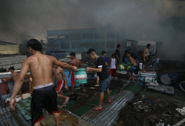 Residents use pails of water to splash on the charred houses after a fire razed through residential area in San Andres Bukid, metro Manila March 12, 2016. (Photo by Romeo Ranoco/Reuters)