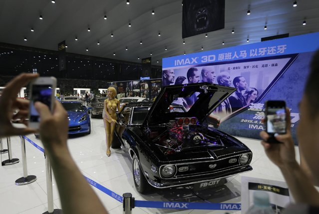 "Visitors to the China's Dream Auto Show take pictures of a woman posing next to a car model which was used for the movie ""Fast and Furious 7"" in Beijing, China, Friday, May 1, 2015. Millions of Chinese are taking advantage of the May Day holidays to visit popular tourist sites. (Photo by Andy Wong/AP Photo)"