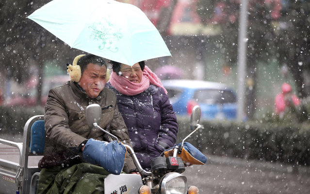 A couple ride a tricycle during a snowstorm along a street in Bozhou, Anhui province, February 5, 2014. According to Xinhua News Agency, snowstorms continued to affect millions of travellers on Thursday as they headed back to work after family reunions at their hometowns during the Chinese lunar New Year holiday.  (Photo by Reuters/China Daily)
