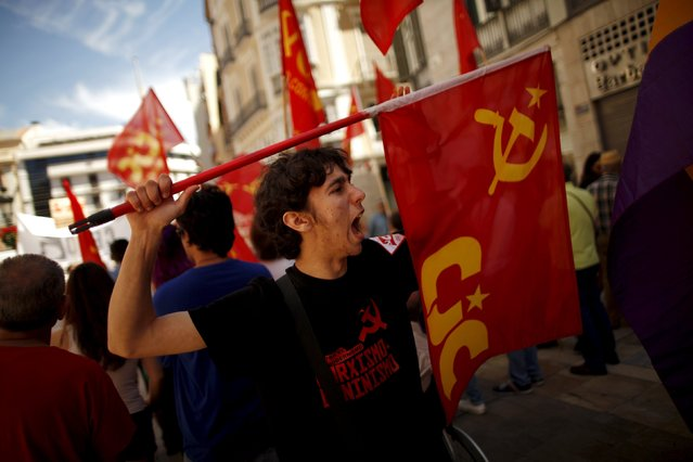 A man holds a Communist flag as he shouts slogans during a May Day rally in Malaga, Spain May 1, 2015. (Photo by Jon Nazca/Reuters)