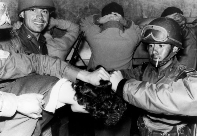 "In this October 3, 1968 file photo, soldiers cut a student's hair as they arrest him during the Tlatelolco massacre in Mexico City. In 1968, students struggled to print up and distribute leaflets and fought the indifference or lies of government-aligned media; the day after the 1968 massacre, newspapers depicted it as an attack on soldiers, with headlines like ""Terrorists and soldiers fought a tough battle"" and ""Criminal provocation causes bloody confrontation"". (Photo by AP Photo)"