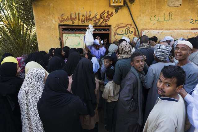 In this Tuesday, April 14, 2015 photo, women and men line up separately as they wait outside to buy bread at a bakery in a village near Abu al-Nasr, about 770 kilometers (480 miles) south of Cairo. Amira, the wife of Salama Osman who works in Cairo without his family most of the year, leaves her village house shortly after dawn everyday to buy bread at the shop. (Photo by Hiro Komae/AP Photo)