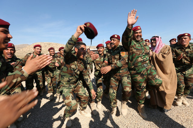 A group of Arab soldiers who have joined Kurdish peshmerga forces celebrate during a graduation ceremony after completing their field training in a training camp in Duhok province, Iraq, February 7, 2017. (Photo by Ari Jalal/Reuters)