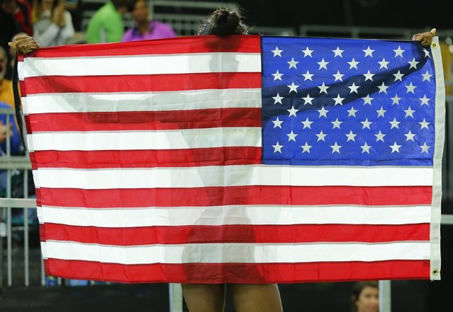 Bronze medalist Quanera Hayes of the U.S. holds up an  American flag as she celebrates after the women's 400 meters final at the IAAF World Indoor Athletics Championships in Portland, Oregon March 19, 2016. (Photo by Mike Blake/Reuters)