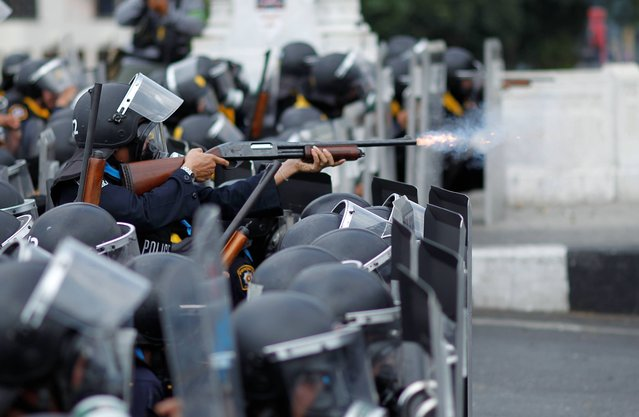 Riot police fire rubber bullets into the crowds of anti-government protesters during a clash in Bangkok, Thailand, Tuesday, February 18, 2014. Emergency medical officials say that one civilian was killed and 50 people were injured in clashes between Thai police and anti-government protesters in Bangkok. (Photo by Wally Santana/AP Photo)