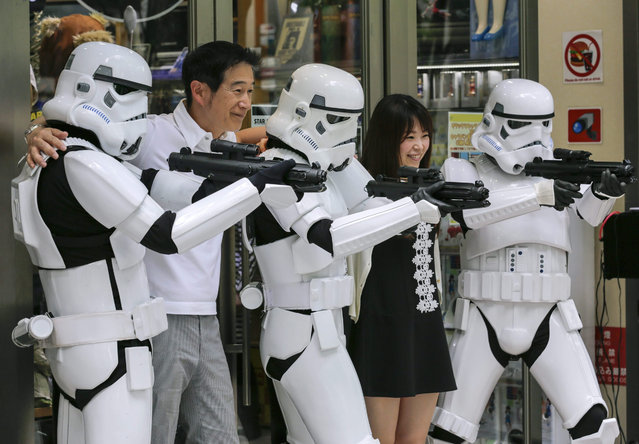 "Fans join with Star Wars' Stormtroopers posing in an appearance for a campaign celebrating ""Star Wars Day"" at a toy shop in Tokyo, Japan, 04 May 2015. May fourth is commemorated for ""May the Force be with you"", the famous words in the movie. (Photo by Kimimasa Mayama/EPA)"