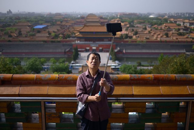 An elderly man uses a selfie stick to take a photo at a park near the Forbidden City in Beijing on May 3, 2015. (Photo by Wang Zhao/AFP Photo)