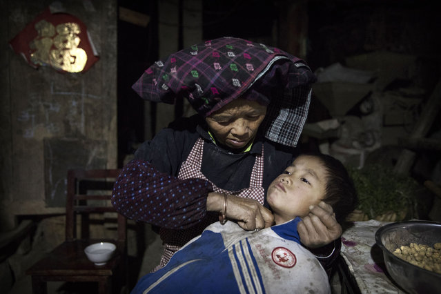 """Grandmother Lu Guoxiu, 64, rubs warm water on the throat of grandson """"left behind"""" child Luo Lie, 5, to help with his cough on December 15, 2016 in Anshun, China. Like millions of Chinese children, the four Luo siblings are being raised by their grandparents in rural China as their parents left to find work in urban areas. While there are no official figures, a recent government report puts the number of 'left behind' children at nearly 10 million, though child welfare experts estimate the number to be closer to 60 million. In the case of the Luo grandparents, who are elderly and poor, they do what they can to meet the basic needs of four children between the ages of 5 and 11. Local schools, educators and community charities often try to the fill the gaps. Still, many children feel the absence of interaction with their mother and/or father, creating a generation of lonely kids who experts worry may be prone to anxiety, poor school performance, and depression. Joining parents in the city is not usually an option, as China's hukou documentation system dictates that education and health care are accessible only in the district where a child is born and registered.  China's government says it is making child welfare a national priority, and will work to improve support to """"left behind"""" children after launching its first-ever national census to assess the problem. (Photo by Kevin Frayer/Getty Images)"""
