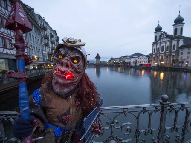 A carnival participant in costume poses in the historic center of Lucerne. (Photo by Sigi Tischler/Keystone)