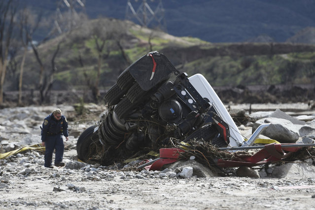 An official looks over the scene, Saturday, February 18, 2017,  where a tractor trailer and a San Bernardino County Fire Department fire engine fell Friday from southbound Interstate 15 where part of the freeway collasped due to heavy rain in the Cajon Pass, Calif.   A huge Pacific storm that parked itself over Southern California and unloaded, ravaging roads, opening sinkholes  eased off Saturday but it was only a temporary reprieve as new storms took aim farther north. (Photo by David Pardo/The Daily Press via AP Photo)