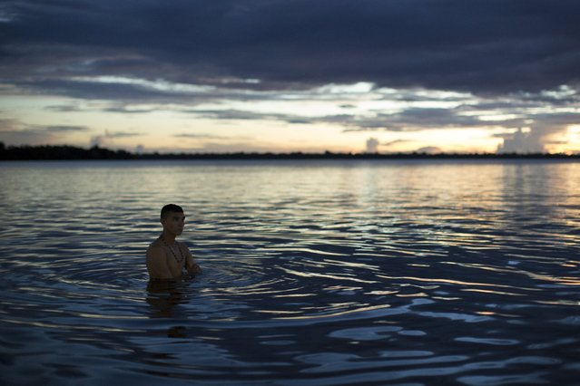 Kambeba Indian, Dream Braga, 18, gets wet at sunset on the banks of the Negro river at the village Tres Unidos, Amazon state May 8, 2015. (Photo by Bruno Kelly/Reuters)