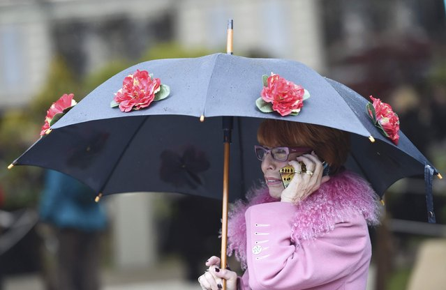 A visitor shelters under her umbrella as she makes a phone call at  the Royal Horticultural Soceity's Chelsea Flower Show in London, Britain, May 18, 2015. (Photo by Toby Melville/Reuters)