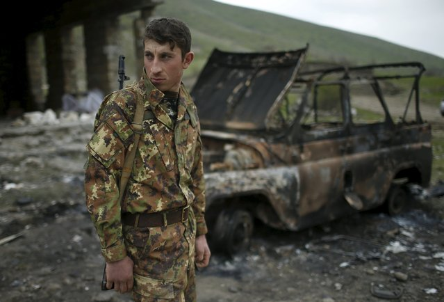 A serviceman of the self-defense army of Nagorno-Karabakh stands next to a destroyed military car in the village of Talish April 6, 2016. (Photo by Reuters/Staff)