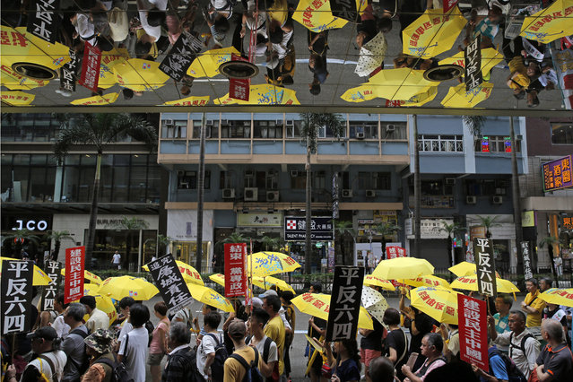 """Pro-democracy protesters carry a banner with Chinese reads """"Vindicate June 4th"""" during a demonstration in Hong Kong, Sunday, May 26, 2019. A vigil will be held on June 4 at the Victoria Park to mark the 30th anniversary of the military crackdown on the pro-democracy movement at Beijing's Tiananmen Square on June 4, 1989. (Photo by Kin Cheung/AP Photo)"""