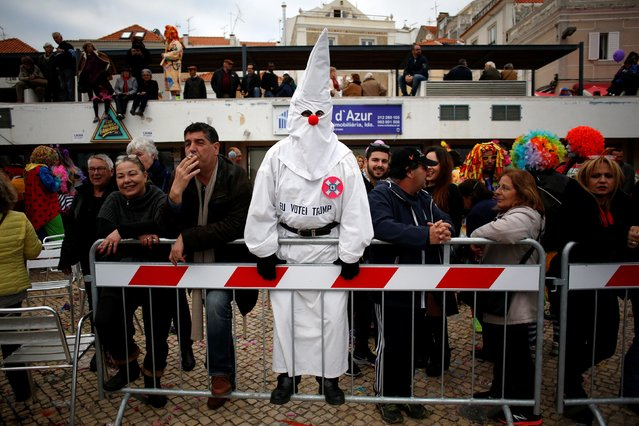 """A man in disguise with the phrase """"I voted Trump""""  stands during the carnival clowns parade in Sesimbra village, Portugal, February 27, 2017. (Photo by Pedro Nunes/Reuters)"""