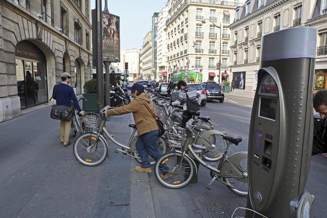 "Tourists take ""Velibs"", self service bicycles, on the Avenue Matignon in Paris, Friday March 14, 2014. The Paris mayor's race will give the city a new leader for the first time in 13 years, and offers a chance to reimagine one of the world's top tourist destinations. (Photo by AP Photo/Remy de la Mauviniere)"
