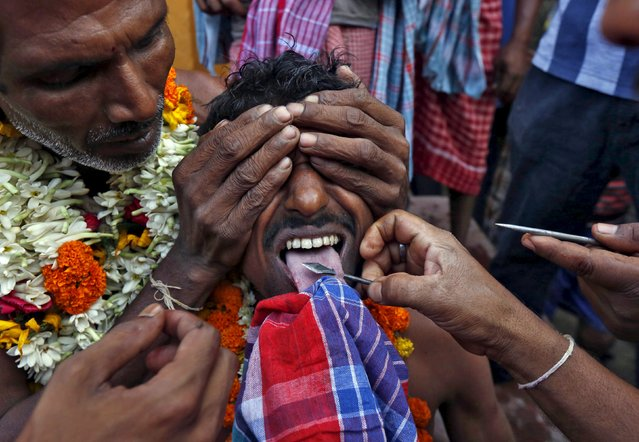 The tongue of a Hindu devotee is pieced with a metal skewer during the annual Shiva Gajan religious festival in Banga village in West Bengal, India, April 13, 2016. Hundreds of faithful devotees offer sacrifices and perform acts of devotion during the festival in the hopes of winning the favour of Hindu god Shiva and ensuring the fulfillment of their wishes, and also to mark the end of the Bengali calendar year. (Photo by Rupak De Chowdhuri/Reuters)