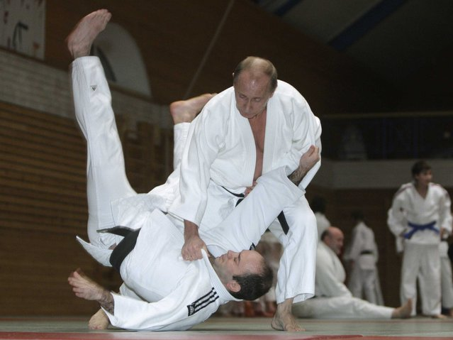 Vladimir Putin, right, conducts a judo training session at Top Athletic School during his working visit to St Petersburg, 18 December 2009. (Photo by Alexei Druzhinin/AFP Photo/RIA Novosti)