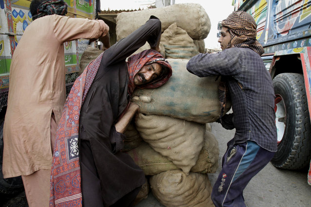 Pakistani loaders help a laborer to carry a sack of potatoes at a fruit and vegetable market in Lahore, Pakistan, Thursday, April 30, 2015. (Photo by K. M. Chaudary/AP Photo)