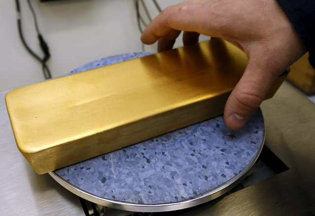 An employee weighs an ingot of 99.99 percent gold at the Krastsvetmet Krasnoyarsk non-ferrous metals plant in the Siberian city of Krasnoyarsk, Russia, June 5, 2015. Krastsvetmet is one of the world's largest players in the precious metals industry. REUTERS/Ilya Naymushin