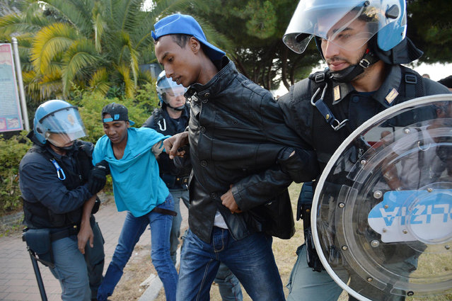 Italian police officers drag away migrants in Ventimiglia, at the Italian-French border Tuesday, June 16, 2015. Police at Italy's Mediterranean border with France have forcibly removed some of the African migrants who have been camping out for days in hopes of continuing their journeys farther north. The migrants, mostly from Sudan and Eritrea, have been camped out for five days after French border police refused to let them cross. (Luca Zennaro/ANSA via AP)