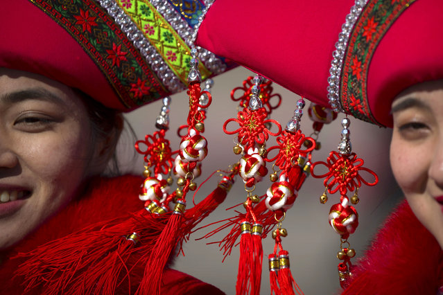 In this Sunday, March 12, 2017 photo, decorations hang from the hats of hospitality staff members as they pose for a group photo during a plenary session of the National People's Congress (NPC) in Beijing. (Photo by Mark Schiefelbein/AP Photo)