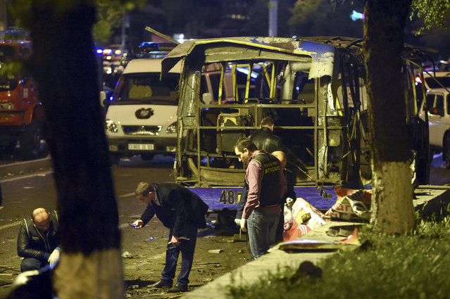 In this Monday night, April 25, 2016 photo, experts search the site of a passenger bus explosion in Halabyan street of Yerevan, Armenia. There was no immediate determination of the cause of the Monday evening explosion in Yerevan several kilometers northwest of the capital's central square. (Photo by Hayk Baghdasaryan/PHOTOLURE Photo via AP Photo)