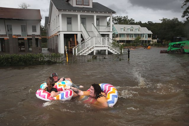 People float down Lakeshore Drive which is covered by water from Lake Pontchartrain after the area flooded in the wake of Hurricane Barry on July 13, 2019 in Mandeville, Louisiana. The storm, which made landfall this morning as a category one hurricane near Morgan City, caused far less damage and flooding than had been predicted. Flash flood watches were issued throughout much of Louisiana and as far east as the Florida panhandle as the storm was expected to dump more than a foot of rain in many areas and up to 25 inches in some isolated locations. Many areas are now expected to get less than half of the original projections. (Photo by Scott Olson/Getty Images)
