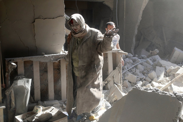 An injured woman reacts at a site hit by airstrikes in the rebel held area of Old Aleppo, Syria, April 28, 2016. (Photo by Abdalrhman Ismail/Reuters)