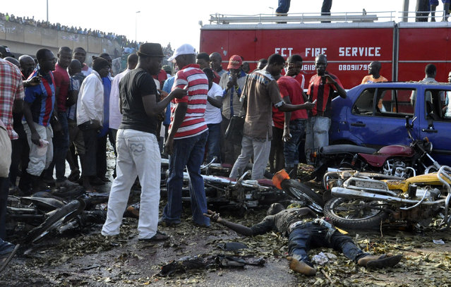 People gather at the site of a blast at the Nyanya Motor Park, about 16 kilometers (10 miles) from the center of Abuja, Nigeria, Monday, April 14, 2014. An explosion blasted through a busy commuter bus station on the outskirts of Abuja before 7 a.m. (06:00 GMT) Monday as hundreds of people were traveling to work. (Photo by Gbemiga Olamikan/AP Photo)