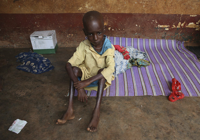 A sick Muslim boy, who is protected by local Christians, sits outside a house in town of Yaloke, northwest of Bangui, April 5, 2014. (Photo by Goran Tomasevic/Reuters)