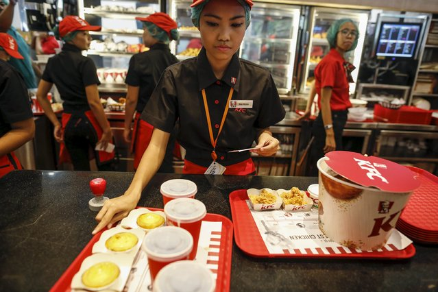 Staff prepare to sell meals at a KFC branch during its opening day in Yangon June 30, 2015. The first KFC branch in Myanmar opened on Tuesday, reported local media. (Photo by Soe Zeya Tun/Reuters)